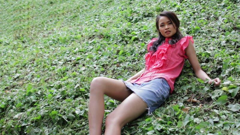 84533c470 Muchacha asiática erótica atractiva con la mini falda en hierba verde.  Exterior, adulto.
