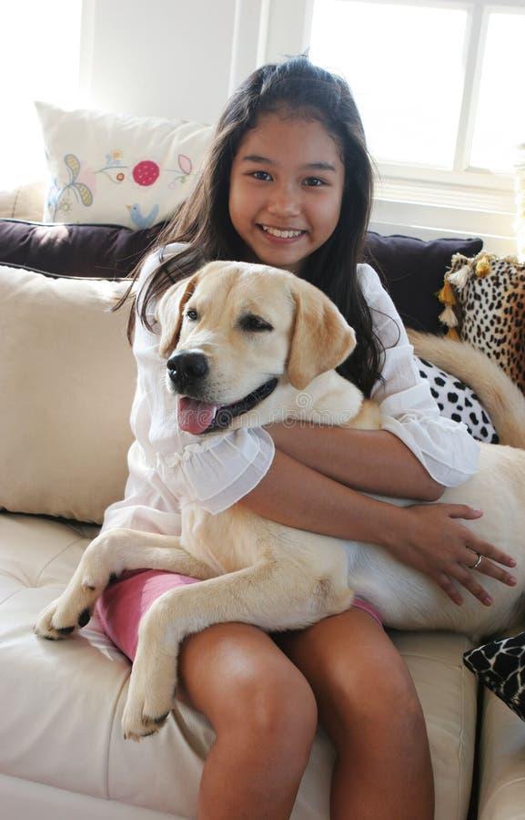 Muchacha asiática feliz con su perro de animal doméstico fotografía de archivo