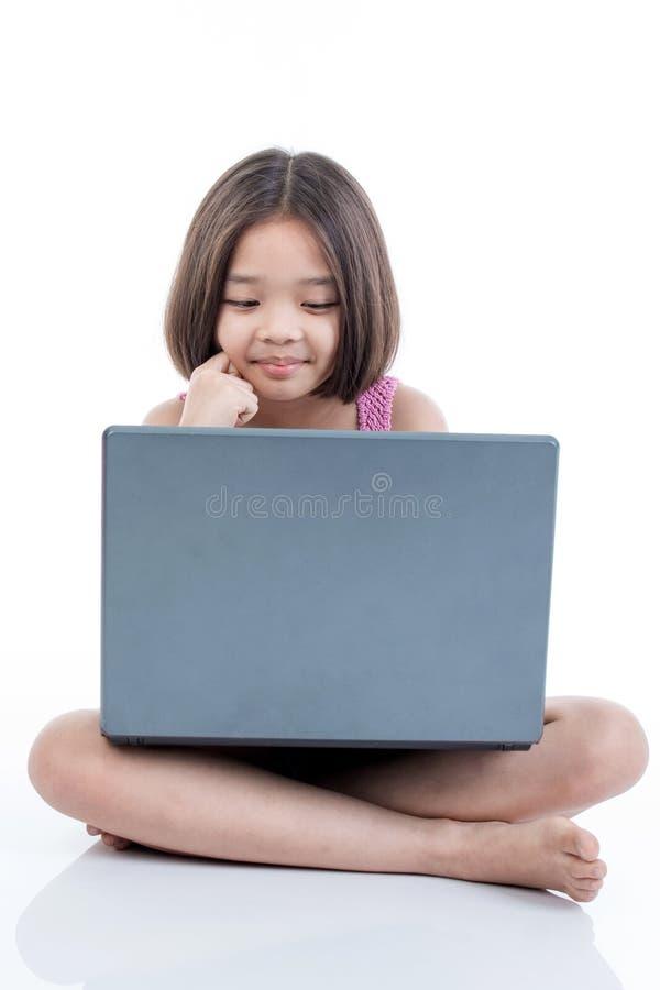 Muchacha asiática feliz del niño que usa el ordenador portátil y el pensamiento imagenes de archivo