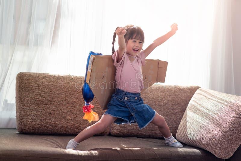 Muchacha asiática feliz del pequeño niño que juega en un traje del astronauta fotografía de archivo libre de regalías