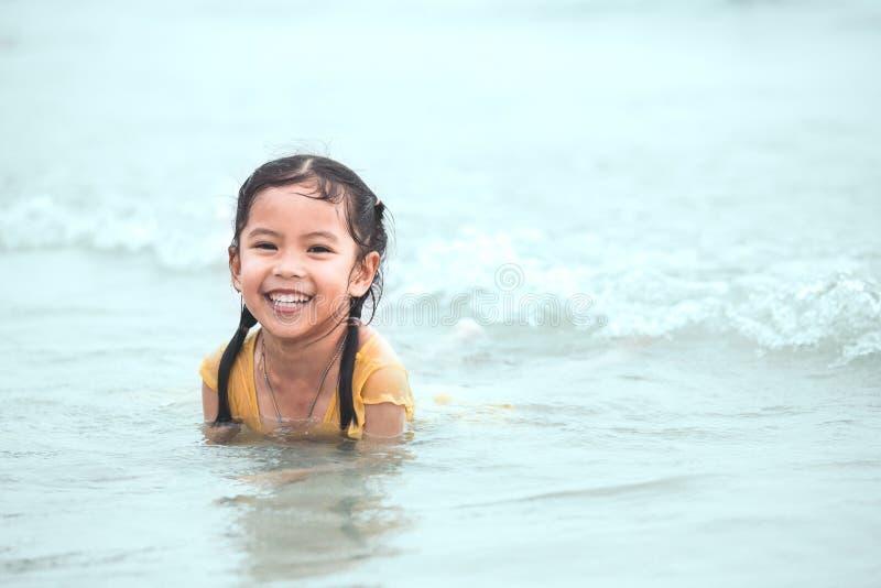 Muchacha asiática feliz del pequeño niño que se divierte para jugar el agua en el mar foto de archivo