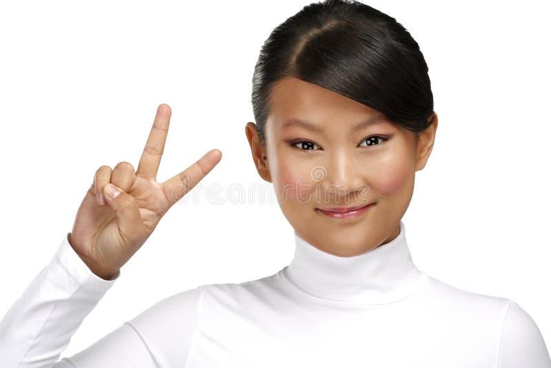 Muchacha asiática feliz hermosa que muestra el signo positivo de la victoria foto de archivo libre de regalías