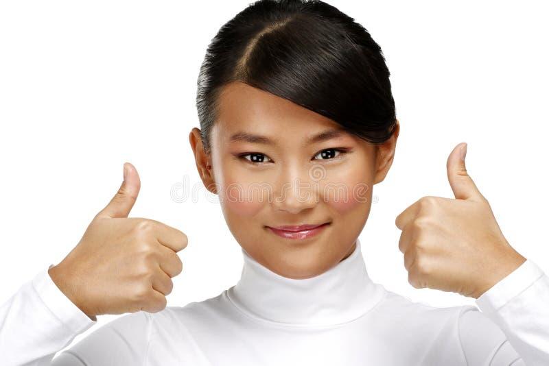 Muchacha asiática feliz hermosa que muestra los pulgares para arriba fotografía de archivo