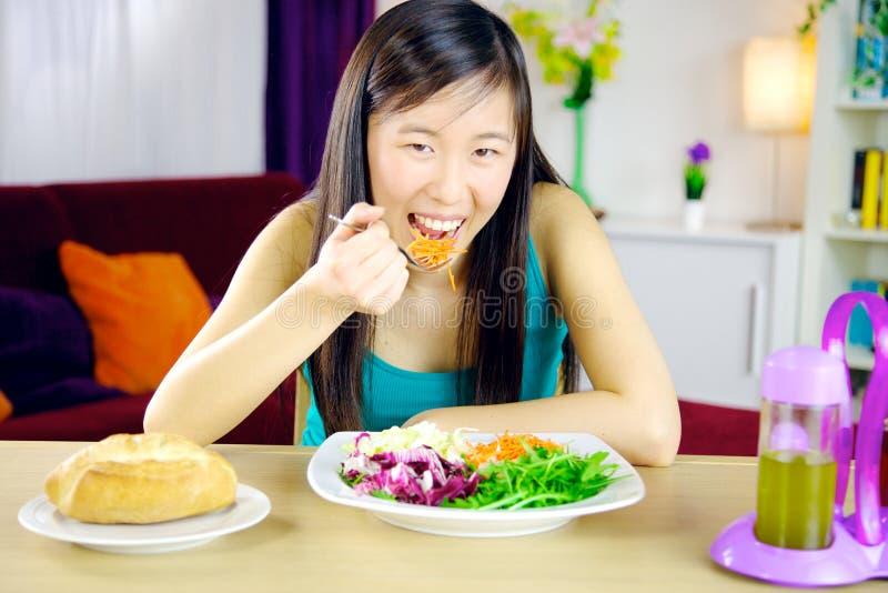 Muchacha asiática feliz que come la ensalada en casa imagenes de archivo