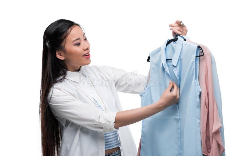 Muchacha asiática feliz que elige las blusas, aisladas en blanco imagen de archivo libre de regalías