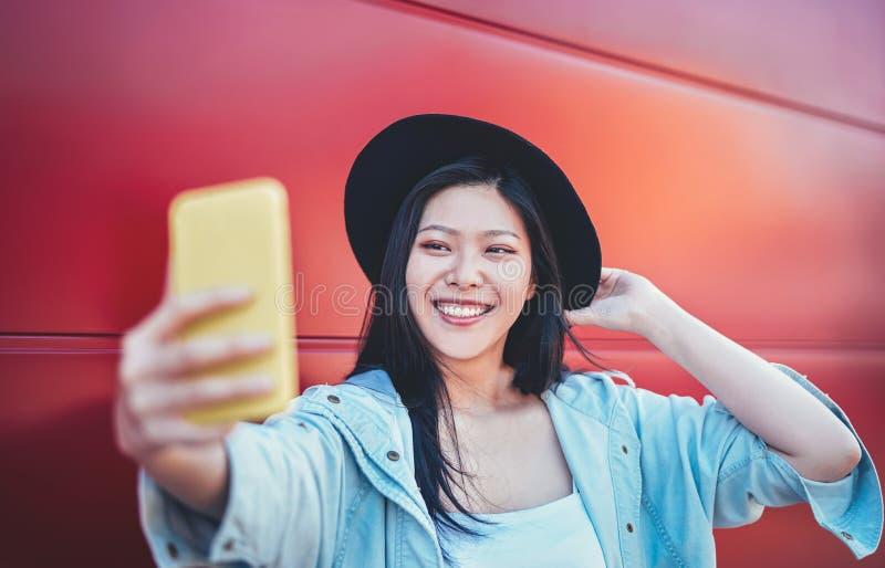 Muchacha asiática feliz que hace una historia video con el teléfono elegante móvil al aire libre - influencer chino de la web de  imagen de archivo