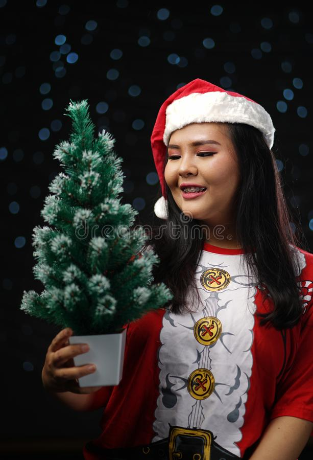 Muchacha asiática feliz que lleva a Santa Costume Holding Small Christmas T fotos de archivo
