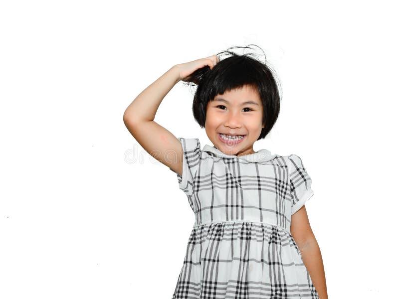 Muchacha asiática feliz que rasguña su cabeza foto de archivo