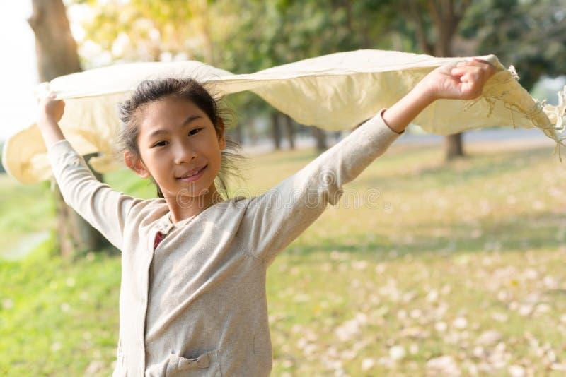 Muchacha asiática feliz que sostiene la bufanda en el parque foto de archivo