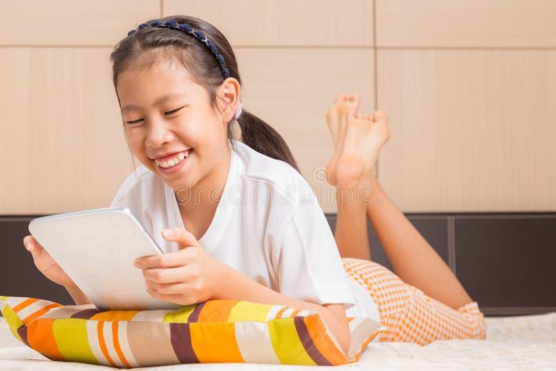 Muchacha asiática feliz que usa la tableta del ordenador foto de archivo