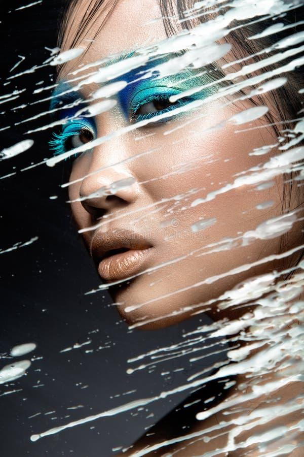 Muchacha asiática hermosa con maquillaje azul brillante detrás del vidrio y de los descensos de la cera Cara de la belleza imagen de archivo libre de regalías