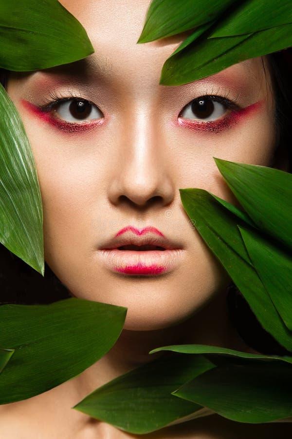 Muchacha asiática hermosa con un arte brillante del maquillaje adentro fotografía de archivo libre de regalías