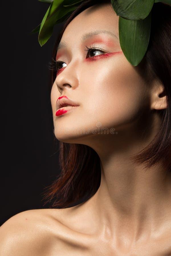 Muchacha asiática hermosa con un arte brillante del maquillaje en hojas verdes Cara de la belleza Imagen creativa imágenes de archivo libres de regalías