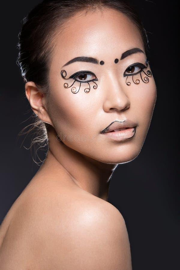 Muchacha asiática hermosa con un maquillaje creativo, papel inusual de las pestañas Cara de la belleza imagen de archivo