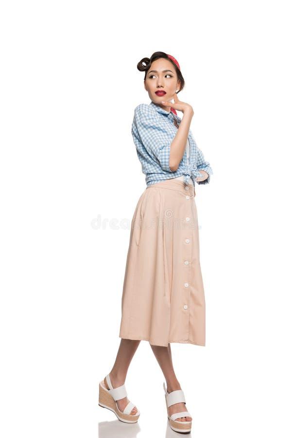 Muchacha asiática hermosa en la falda y la blusa que presentan y que miran lejos fotografía de archivo libre de regalías