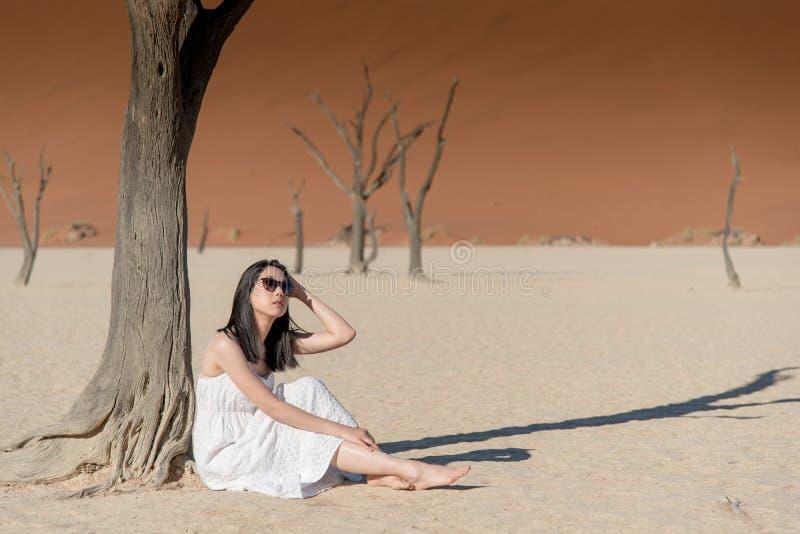 Muchacha asiática hermosa joven en el vestido blanco que se sienta en el deadvlei, N fotos de archivo
