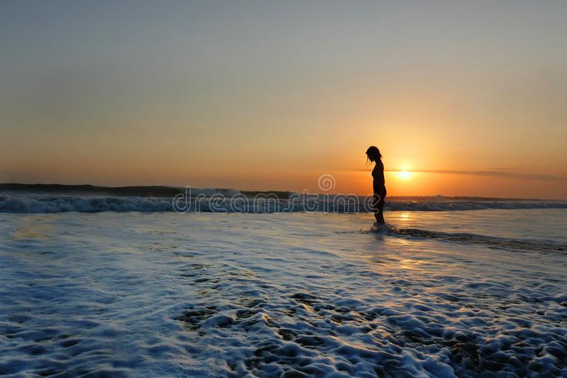 Muchacha asiática hermosa joven solamente en la orilla de mar que mira puesta del sol anaranjada del cielo sobre el océano imágenes de archivo libres de regalías