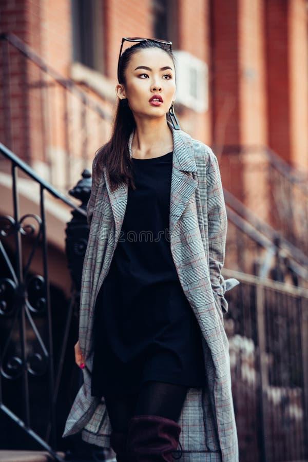 Muchacha asiática hermosa que camina en la calle urbana de la ciudad que lleva la ropa de moda fotografía de archivo