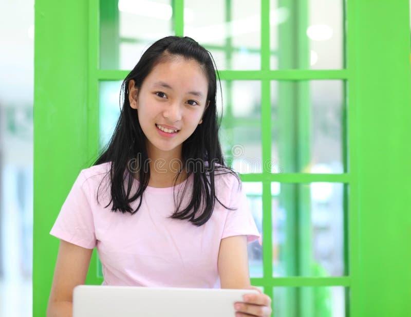 Muchacha asiática hermosa que sonríe y que usa el ordenador portátil foto de archivo