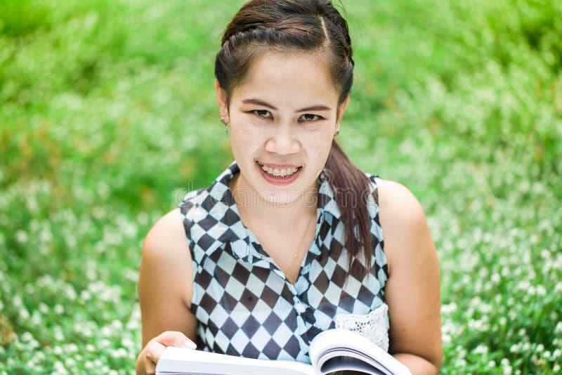 Muchacha asiática hermosa que sostiene un libro abierto imágenes de archivo libres de regalías