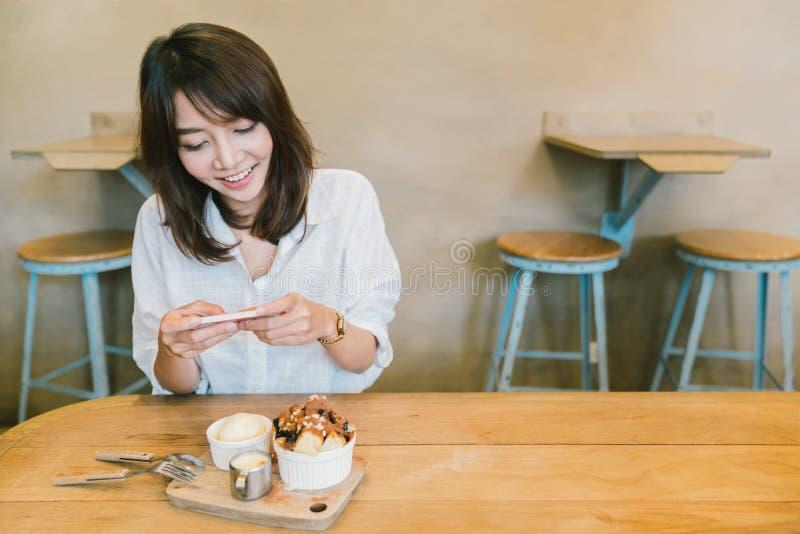 Muchacha asiática hermosa que toma la foto de la torta, del helado, y de la leche de la tostada del chocolate en la cafetería Afi foto de archivo