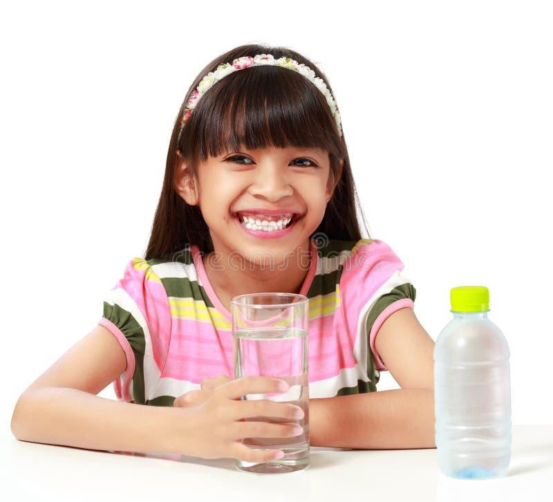 Muchacha asiática joven con el uno-vidrio de agua imagen de archivo