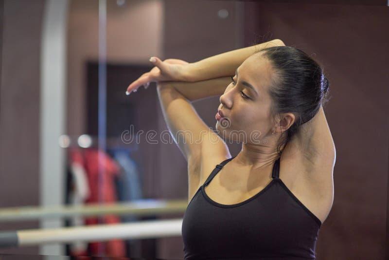 Muchacha asiática joven en gimnasio de la aptitud Mujer joven que hace estirar fotografía de archivo libre de regalías