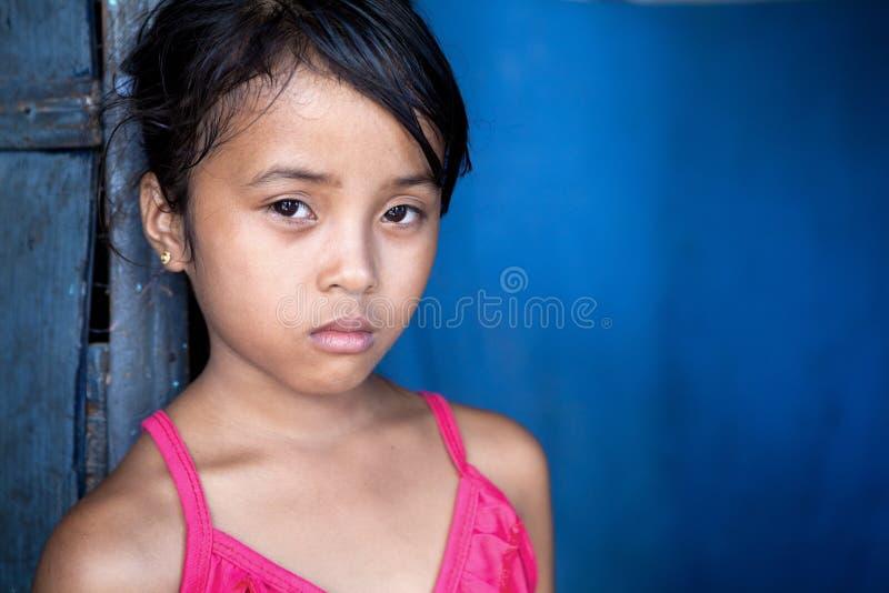Muchacha asiática joven en pobreza sobre azul imagen de archivo