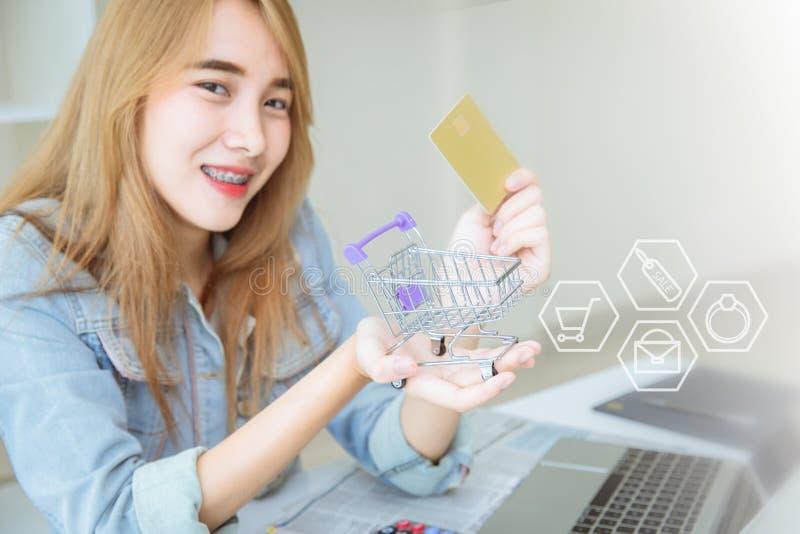 Muchacha asiática joven feliz usando tarjeta de crédito a las compras en línea fotografía de archivo libre de regalías