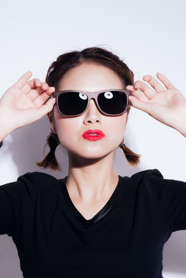 Muchacha asiática joven que hace la emoción Vestido en una camisa negra y una falda amarilla, vidrios y labios brillantes, ropa d fotografía de archivo