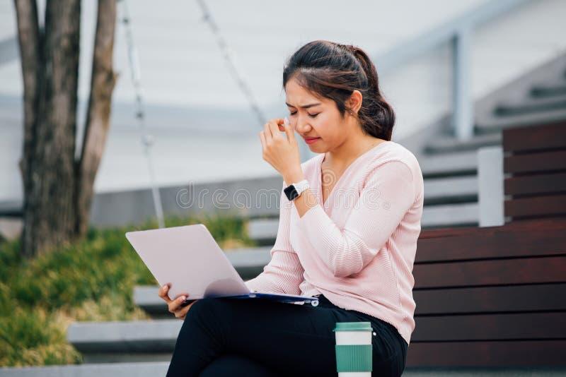 Muchacha asiática joven que llora en pena con el ordenador portátil en su revestimiento en el edificio del campus universitario fotografía de archivo libre de regalías
