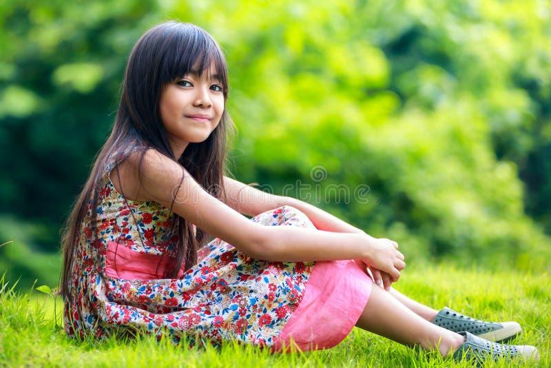Muchacha asiática joven que se sienta en el verde imágenes de archivo libres de regalías
