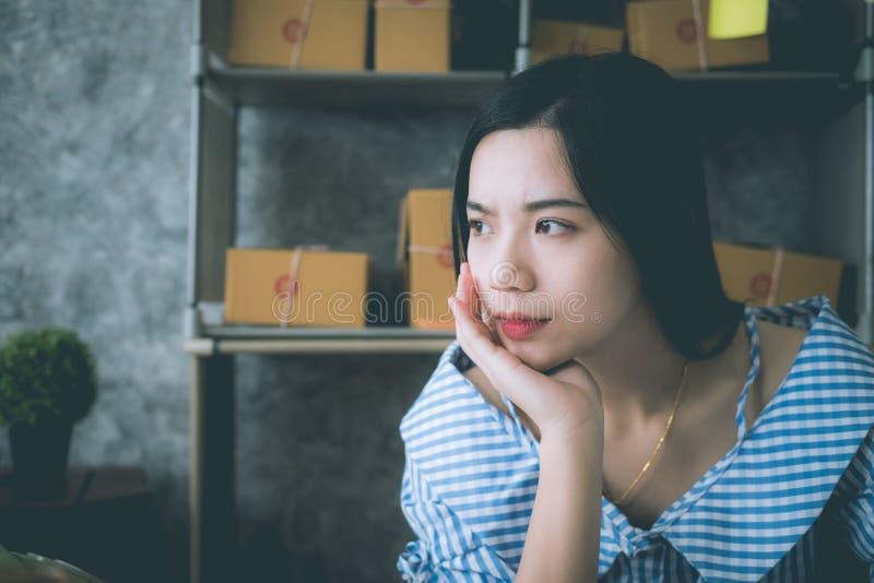 Muchacha asiática joven que trabaja en un ordenador portátil en una pequeña empresa media fotos de archivo