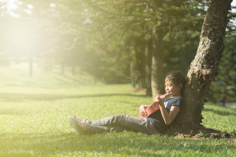 Muchacha asiática joven y feliz que juega con la guitarra del ukelele en el parque por mañana soleada imagen de archivo