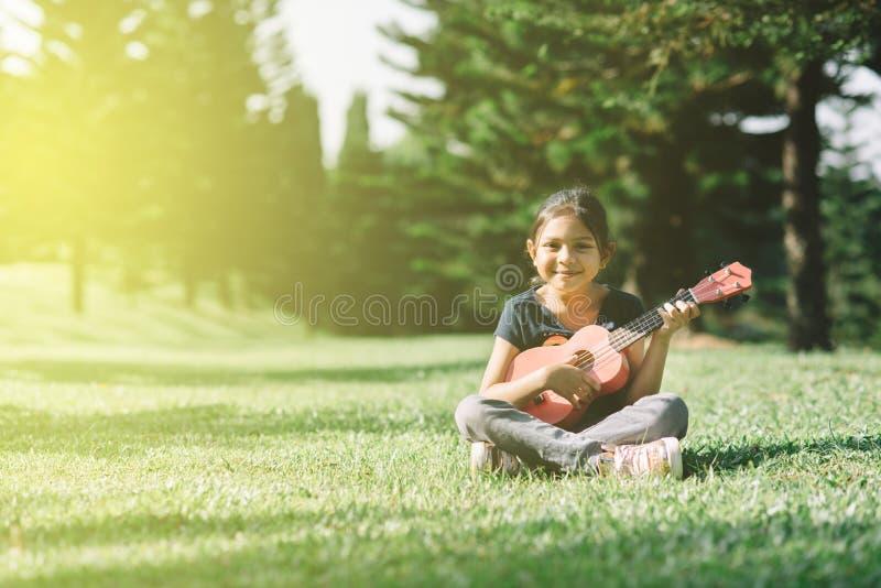 Muchacha asiática joven y feliz que toca la guitarra del ukelele en el parque en la mañana soleada mientras que mira la cámara imagen de archivo