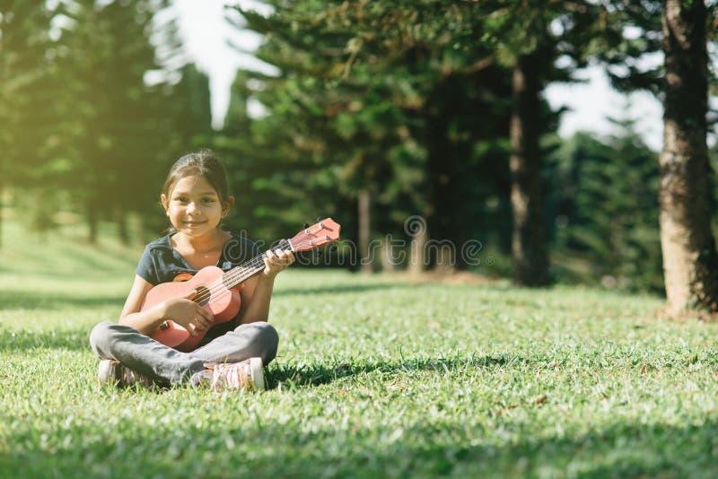 Muchacha asiática joven y feliz que toca la guitarra del ukelele en el parque en la mañana soleada mientras que mira la cámara foto de archivo libre de regalías
