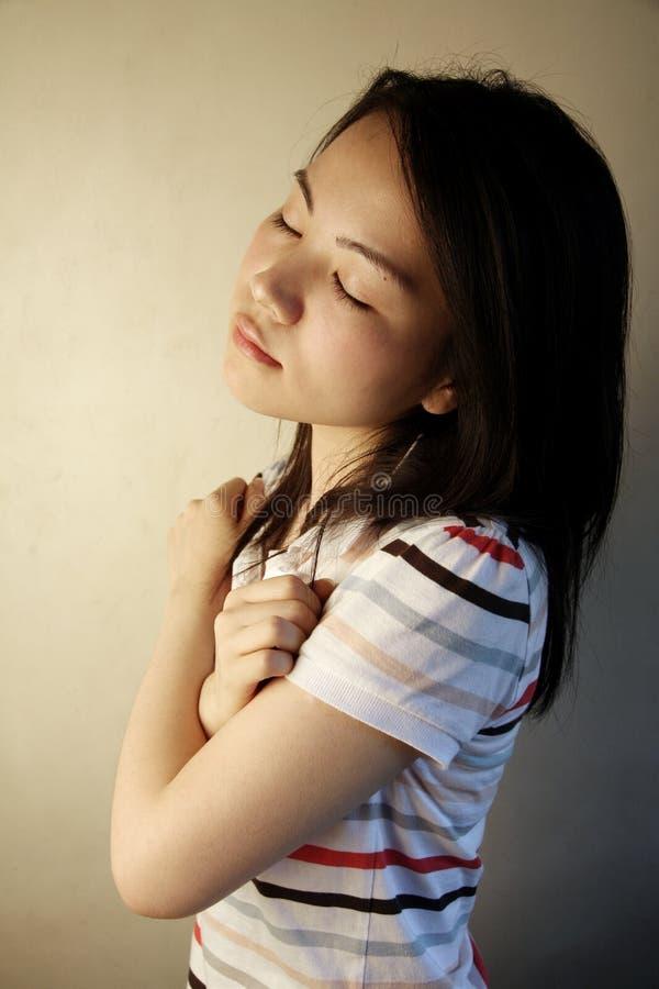 Muchacha asiática linda con sus ojos cerrados foto de archivo