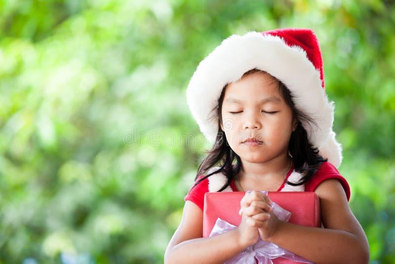 Muchacha asiática linda del niño en el sombrero rojo de santa que sostiene el regalo de la Navidad imágenes de archivo libres de regalías