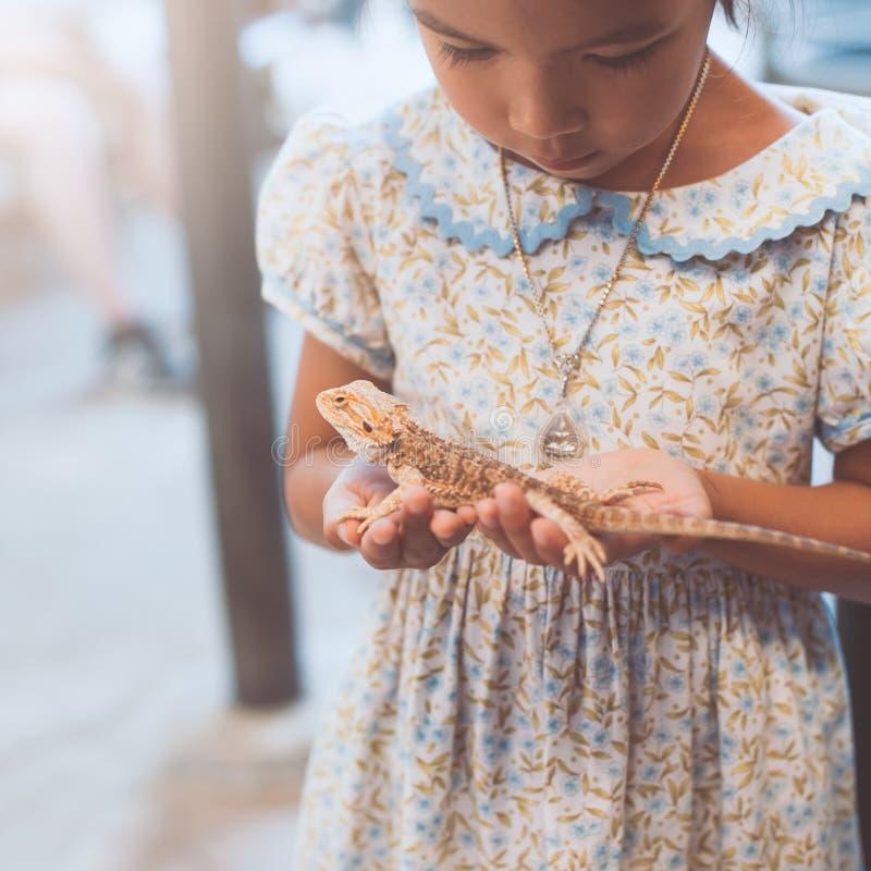 Muchacha asiática linda del niño que se sostiene y que juega con el camaleón fotografía de archivo libre de regalías