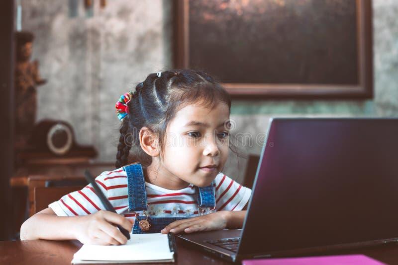 Muchacha asiática linda del niño que usa el ordenador portátil y escribiendo en su cuaderno fotografía de archivo libre de regalías