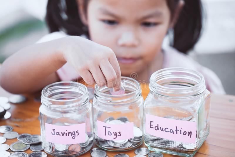 Muchacha asiática linda del pequeño niño que pone la moneda en la botella de cristal imagen de archivo libre de regalías