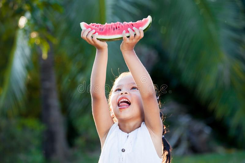 Muchacha asiática linda del pequeño niño que sostiene la fruta fresca de la sandía fotografía de archivo