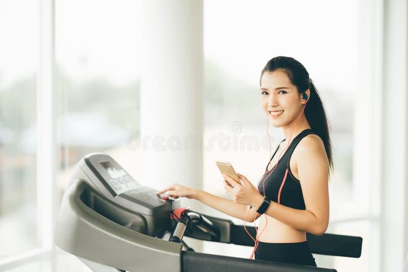 Muchacha asiática linda en la rueda de ardilla en el gimnasio que escucha la música en smartphone vía el auricular del deporte imagenes de archivo