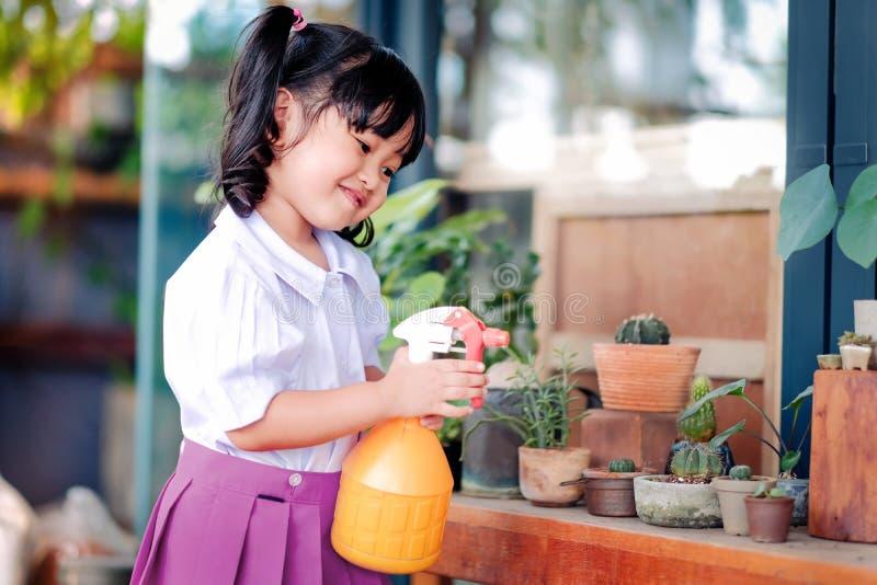Muchacha asiática linda feliz que goza con actividades que cultivan un huerto, un Thre imagen de archivo libre de regalías