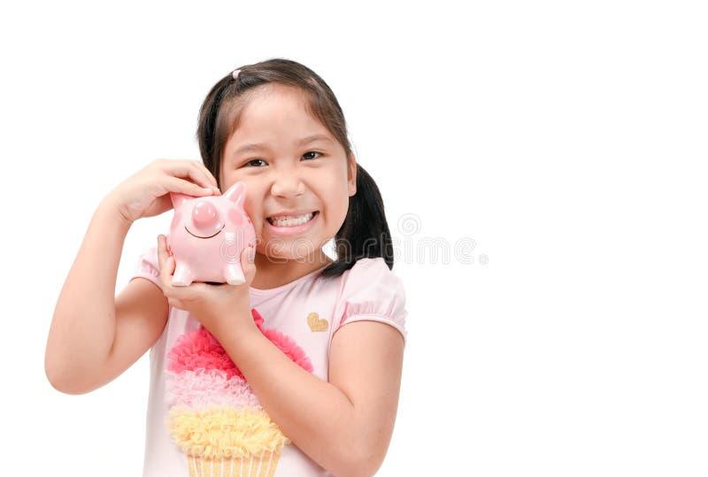 Muchacha asiática linda feliz que sostiene la hucha rosada foto de archivo libre de regalías