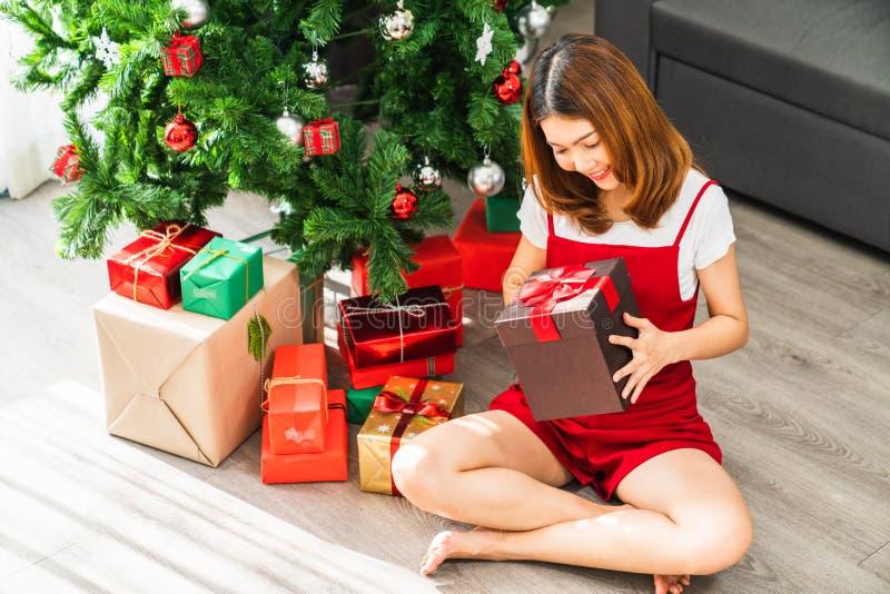Muchacha asiática linda joven que lleva a cabo caja del Mas de X rojo 'actual, árbol de navidad adornado con la sala de estar del foto de archivo