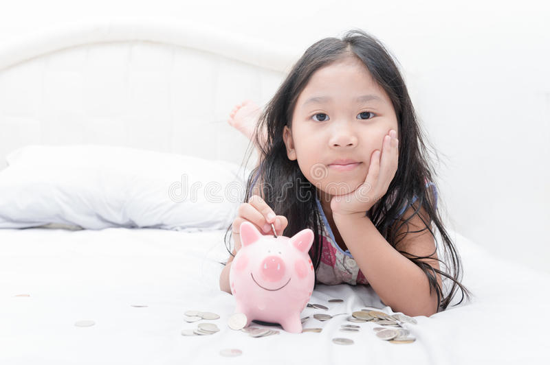 Muchacha asiática linda que pone la moneda a la hucha en cama fotografía de archivo