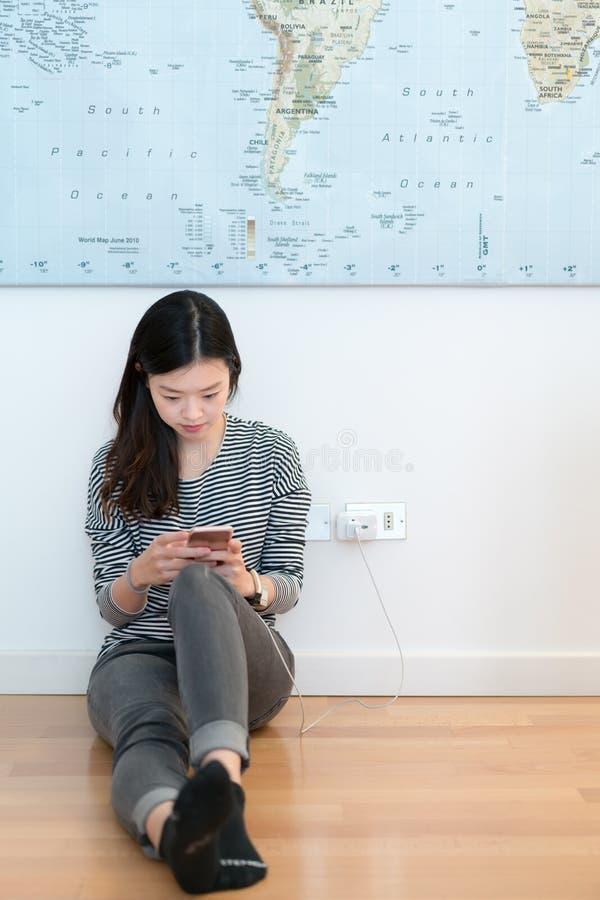 Muchacha asiática linda que usa smartphone mientras que carga imagenes de archivo