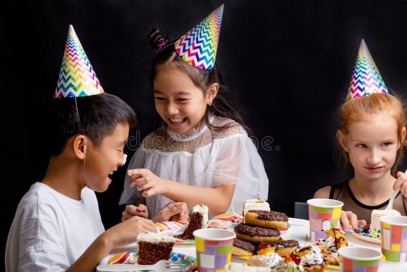 Muchacha asiática positiva ponting en la nariz de los bpy manchada en torta imagen de archivo