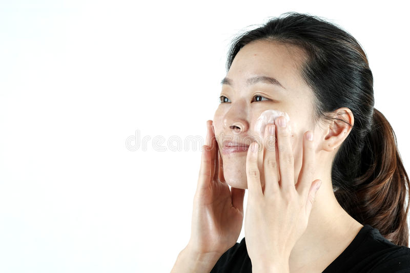 Muchacha asiática que aplica la loción poner crema en la cara, aislada en el fondo blanco imágenes de archivo libres de regalías